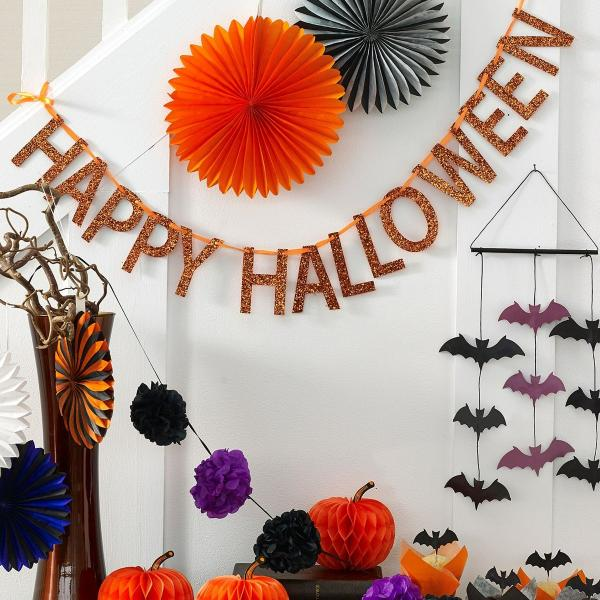 A white hallway decked with paper and glitter garlands for Halloween
